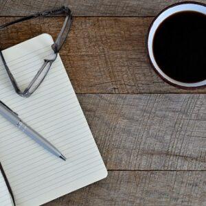 boli gafas notas cafe sobre fondo madera oscuro