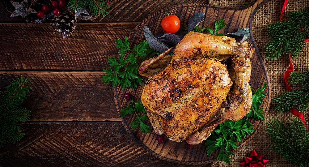 pollo relleno sobre fondo madra oscura con motivos navideños